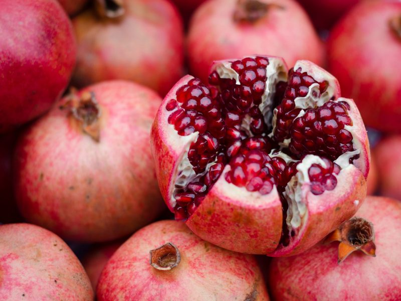 natural background of sweet fresh coral red pomegranate ripes, group of pomegranates. pomegranate closeup, background